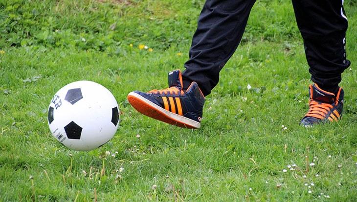 мальчик пинает мяч в траве