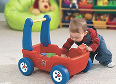 ребенок в год играет с машинкой